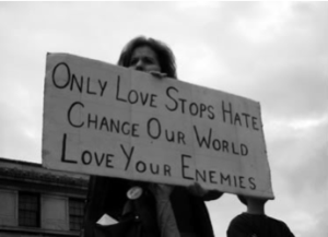 "Woman holding protest sign which reads ""love your enemies."""
