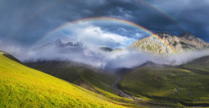 Rainbow in mountain valley during sunset. Beautiful natural landscape