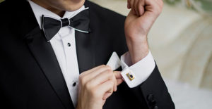 Man in Tux, adjusting cufflinks.