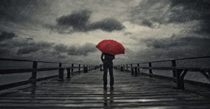 Person standing on dock with red umbrella watching on coming storm