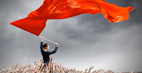 Woman standing above crowd waving red flag