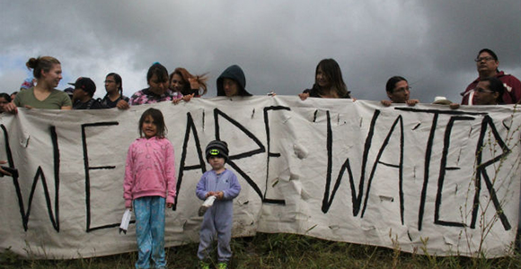 """banner being held stating """"we are water"""""""