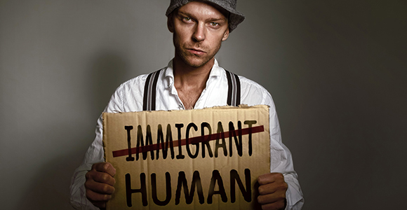 Picture of migrant male with a sign which states human not immigrant