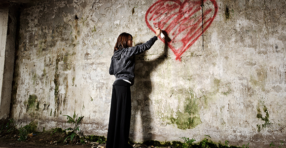 girl spray painting a graffiti heart on wall
