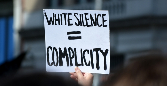 Protest sign stating white silence equals complicity