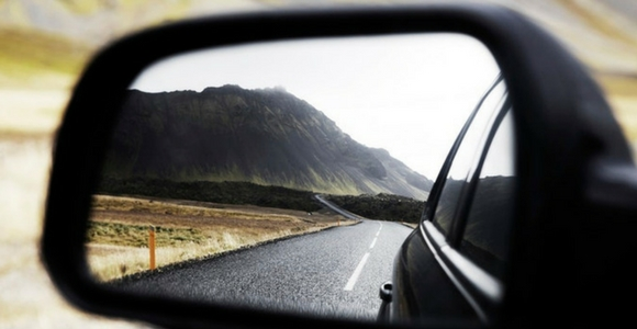 Picture of road and mountain in rearview mirror.